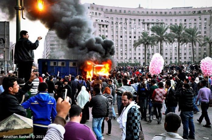 En politibil i flammer under opptøyer i Kairo mandag. Foto: Jonathan Rashad, Flickr.com