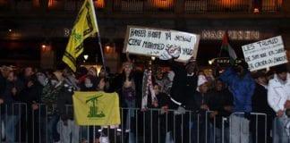 Utenfor Stortinget 8. januar 2009: Flagg for terrororganisasjonen Hizbollah og plakat som minner jødene (yehud) om Hayber (sted hvor jøder ble drept og fordrevet på 600-tallet). «Muhammeds hær vil komme tilbake» truer siste setning. Stein og andre tunge gjenstander regnet ned over venner av Israel, som avholdt en fredelig markering utenfor Stortinget. (Foto: Odd Østtveit)