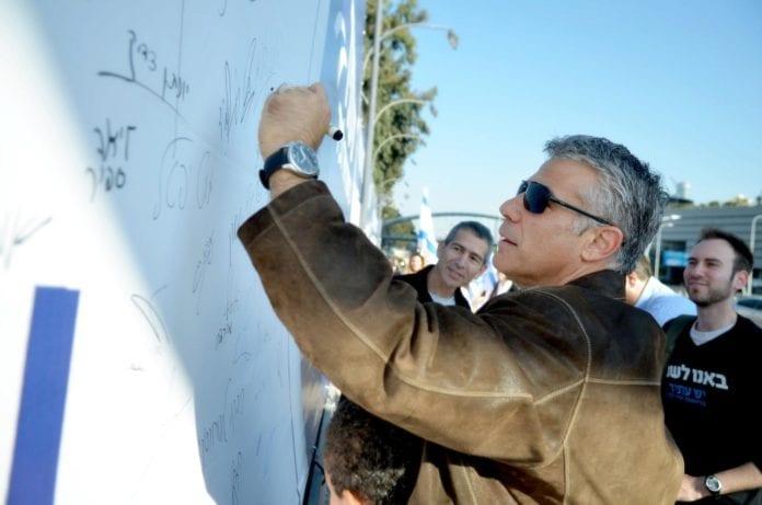 Yair Lapid signerer en av Yesh Atids valgkampplakater for full allmenn verneplikt. (Foto: Yair Lapids Facebook-side)