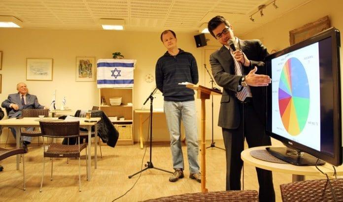 Israels ambassaderåd George Deek (t.h.) holder foredrag på møte i MIFF Drammen 7. februar 2013. Conrad Myrland, daglig leder i MIFF, er tolk. Til venstre sitter Karl Frode Hilton, leder av MIFF Drammen. (Foto: Alexander Bekkevold)