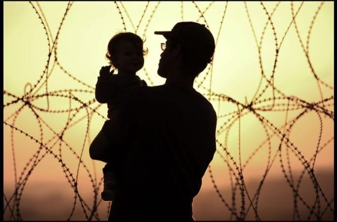 Far og barn innegjerdet i en israelsk bosetning på Vestbreddet. (Illustrasjon: Rusty Stewart, flickr.com)