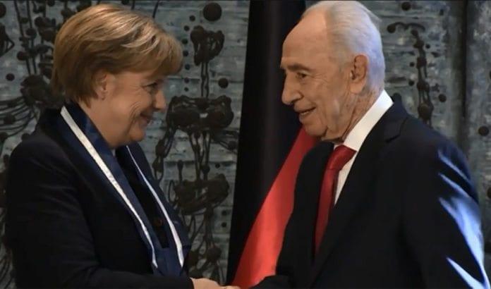Her mottar Angela Merkel æresmedalje fra Shimon Peres. Foto: Skjermdump fra Youtube.