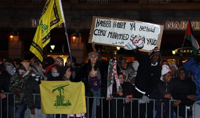 Da Israel-venner holdt en støttemarkering for Israel i Oslo 8. januar 2009 holdt noen av motdemonstrantene opp dette banneret. Teksten er en trussel om å gjenta Muhammeds massakre av de tre jødiske stammene i Hayber. Legg også merke til de gule flaggene for terrororganisasjonen Hizbollah. (Arkivfoto: Odd Østtveit)