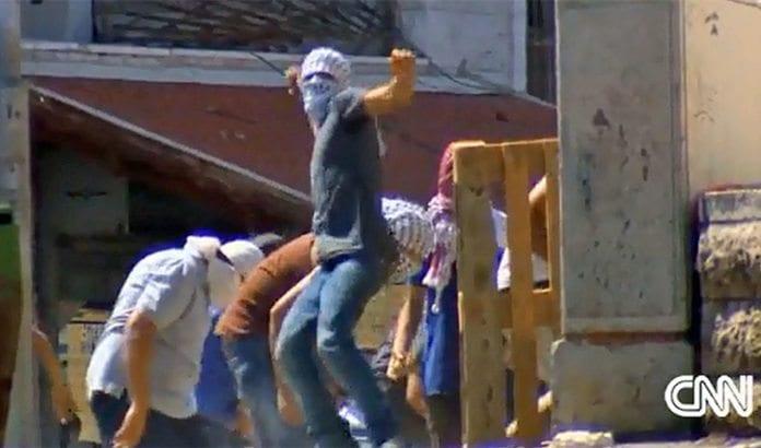 Maskerte palestinere kaster stein mot israelsk politi i Jerusalem. (Foto: Skjermdump fra CNN 6. juli 2014)