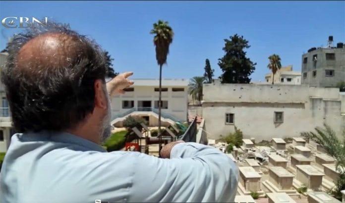 Erkebiskop Alexios peker mot stedet der raketter har blitt avfyrt fra kirkens område. (Foto: Skjermdump fra CBN)