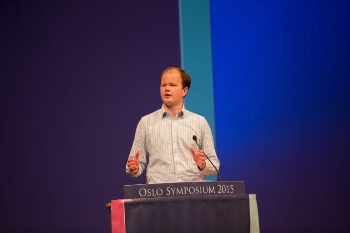 Conrad Myrland taler på Oslo Symposium i mars 2015. (Foto: Tor-Bjørn Nordgaard, MIFF)