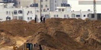 Væpnede og maskerte menn fra Hamas graver ved grensegjerdet mot Israel. (Foto: Skjermdump fra Ynetnews.com web-tv)