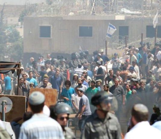 Aktivister som prøver å stanse rivningen konfronterer sikkerhetsstyrker i Beit El. (Foto: Hillel Meir, Tazpit via Jpost.com)