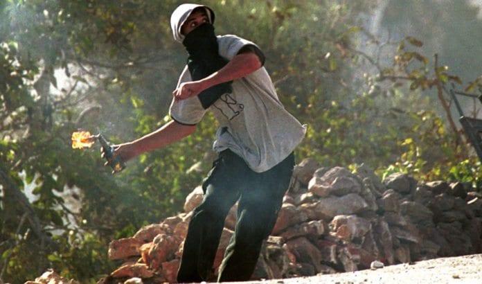 En maskert palestiner kaster en molotov-coctail. (Illustrasjonsfoto: Flash90)