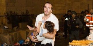 En liten gutt blir båret bort fra åstedet etter terrorangrepet i Jerusalem 3. oktober. Guttens far ble drept i angrepet. (Foto: Yonatan Sindel, Flash90)