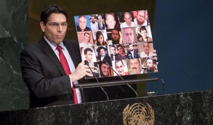 Israels FN-ambassadør Danny Danon holdt opp plakat med bilder av høstens israelske terrorofre for FNs generalforsamling i fjor.(Foto: FN)