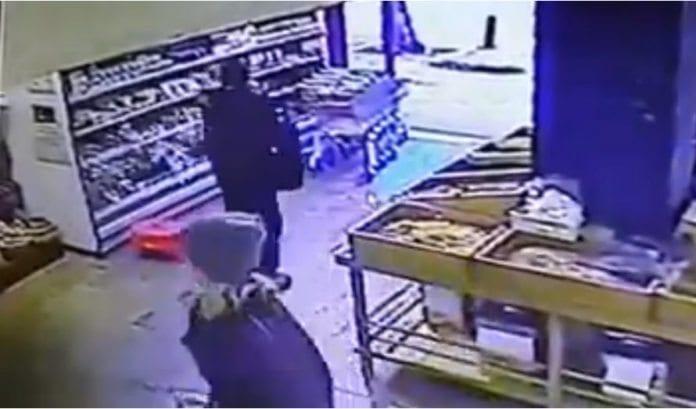 Overvåkningsfilm viser angriperen som plukker opp noen nøtter, legger dem tilbake, tar ut skytevåpen fra ryggsekken sin og begynner å skyte utenfor butikken. (Skjermdump via Jpost.com)