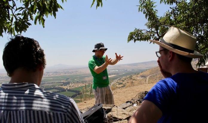 Den israelske guiden forteller om Golanhøyden. I bakgrunnen er grenseområdet mellom Israel og Syria. (Foto: Bjarte Bjellås)