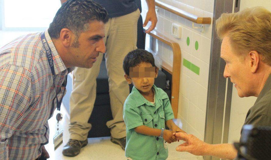Conan O'Brien snakker med sosialarbeider Fares Issa. I midten en syrisk gutt som har fått hjelp på sykehuset. (Foto: Privat)