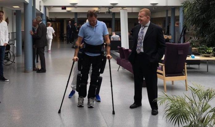 Ryggmargsskadde Knut Ølstad tester ut ReWalk mens ambassadør Raphael Shutz følger med. (Foto: Den israelske ambassaden)