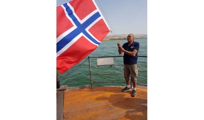 Første dag på turen: Tjue forventningsfulle nordmenn med båt utover Gennesaretsjøen. «Ja, vi elsker» – medan flagget går til topps.