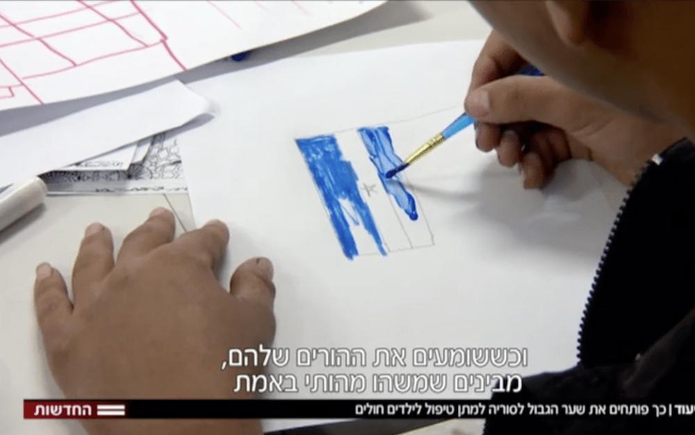 Et syrisk barn tegner et israelsk flagg på sykehuset i Israel. (Foto: Skjermdump Hadashot)