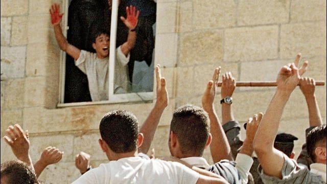 Palestineren Aziz Salha deltok i Ramallah-lynsjingen. Her viser han de to israelernes blod til den jublende folkemengden. Israel løslot ham i Gilad Shalit-utvekslingen i 2011. (Foto: Via PMW)