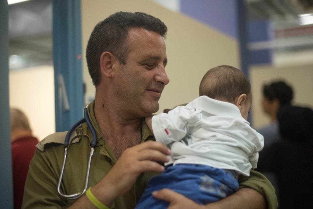 En israelsk helsearbeider med et syrisk barn. (Foto: IDF)