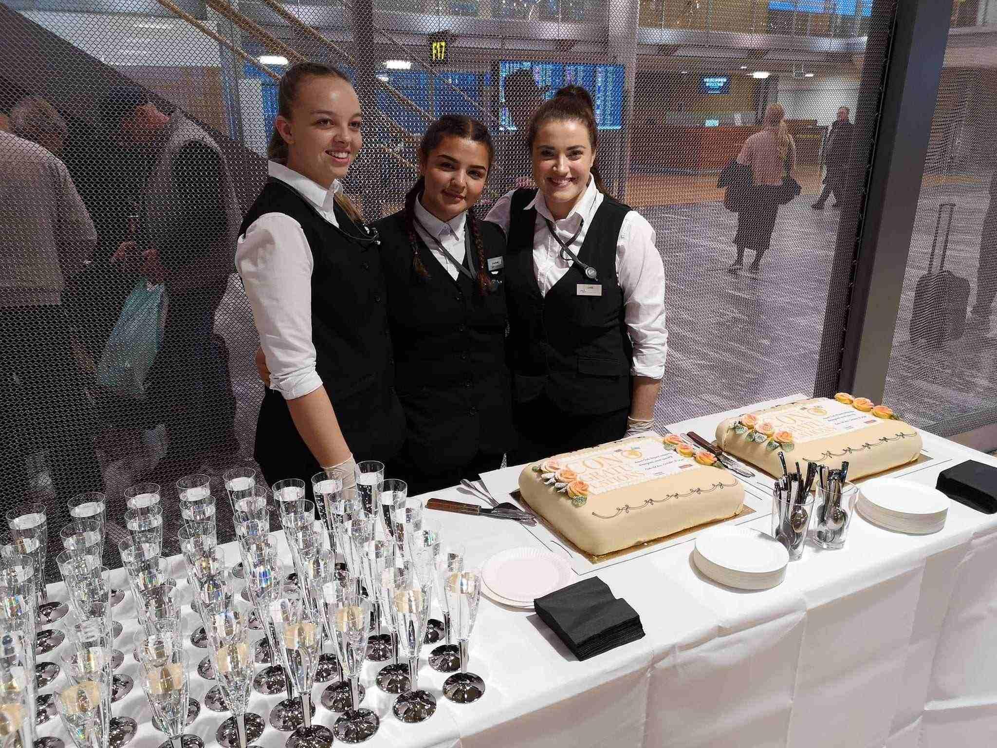 Kake og drikke blir servert av disse unge damene fra Norwegian.
