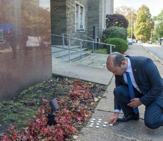 Israels diasporaminister Naftali Bennett tenner et lys utenfor synagogen som ble angrepet lørdag. (Foto: Facebook)